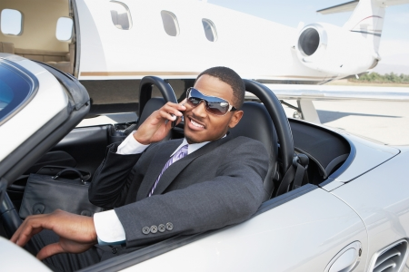 private jet: Man sitting in Convertible near private jet talking on mobile LANG_EVOIMAGES