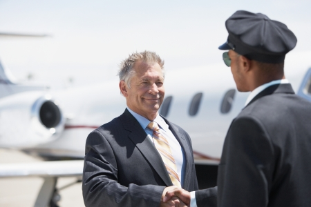 private jet: Businessman Beside private jet shaking hands with pilot