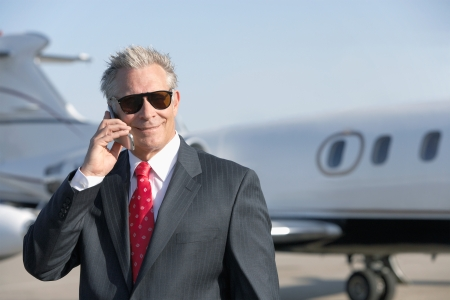 private jet: Businessman standing on landing strip near private jet talking on mobile