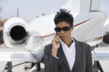 民間の飛行機の前に立っていると電話で話している半ば大人のアフリカ系アメリカ人実業家。 写真素材 - 18833747