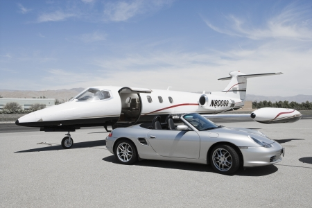 Convertible and private jet on landing strip. LANG_EVOIMAGES