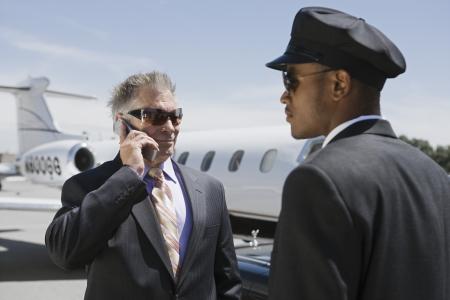 シニア ・ ビジネスマン立って外のプライベート ジェットと運転手を支援、電話で話しています。 写真素材