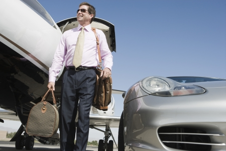 business travel: Mid-adult businessman in front of car and airplane.