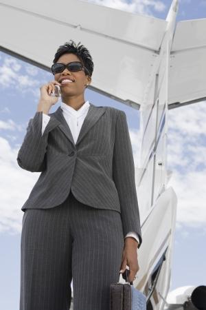 飛行機の前で携帯電話を使用して半ば大人実業家。 写真素材