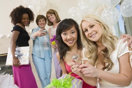 花嫁友人の示す大きな婚約指輪ブライダル シャワーで座っています。
