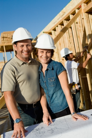 two people with others: Couple in hard hats with blueprint on house construction site portrait LANG_EVOIMAGES