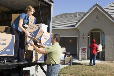 middle easterners: Man and woman unloading truck of cardboard boxes