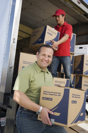middle easterners: Portrait of man unloading with worker truck of cardboard boxes