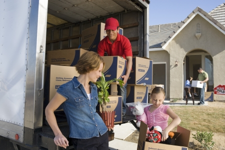 moving truck: Family and worker unloading truck of cardboard boxes