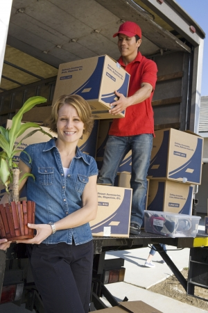 moving truck: Portrait of woman unloading with worker truck of cardboard boxes LANG_EVOIMAGES