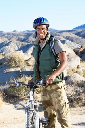 young man standing: Giovane uomo in piedi con la mountain bike di fronte colline