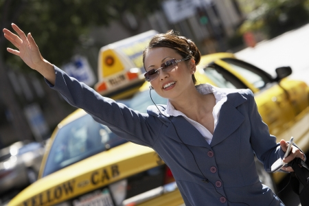 hailing: Businesswoman Hailing Cab using Cell Phone with hands free