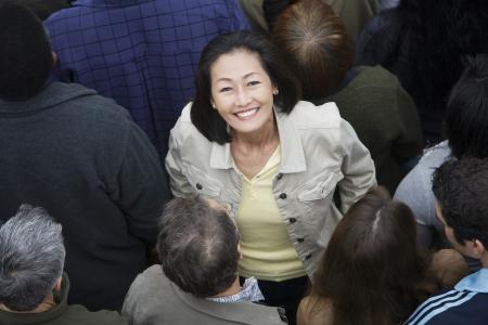 mixed age range: Mujer de pie entre la muchedumbre