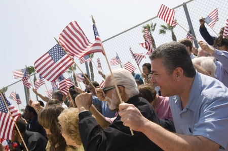 american flag waving: Crowd holding American flags LANG_EVOIMAGES
