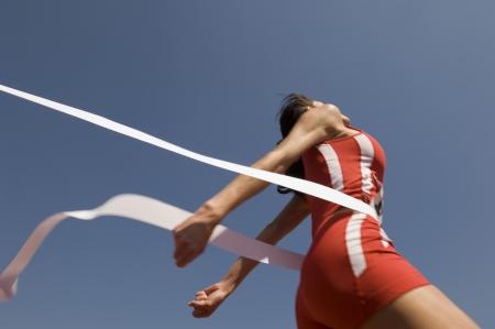 finishing line: Female track athlete crossing finishing line