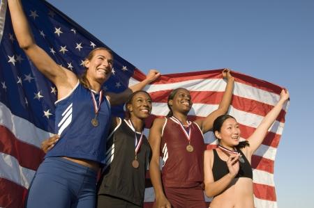 4 つの女性選手を祝うとアメリカの国旗を保持しています。 写真素材
