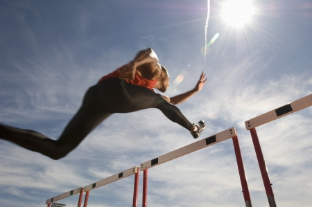 jumping: Runner jumping over running hurdle, low angle view