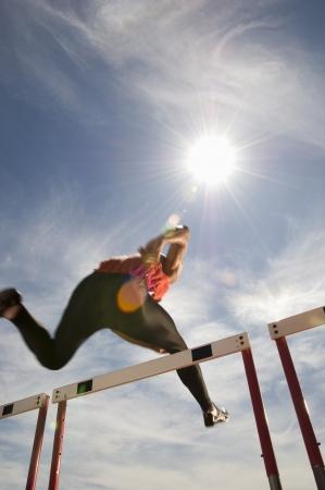 Runner sautant par-dessus course obstacle, faible angle de vue