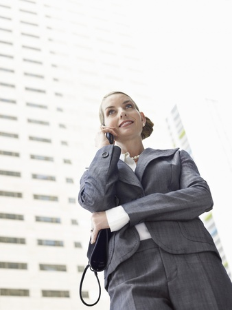 Businesswoman using mobile phone outdoors Stock Photo - 18884502