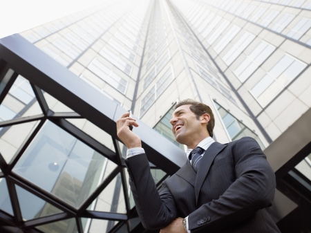 building business: Businessman reading message on phone outside office (low angle view)