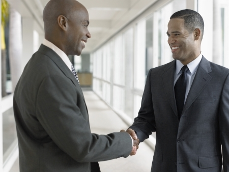 negotiation business: Businessmen shaking hands in hallway