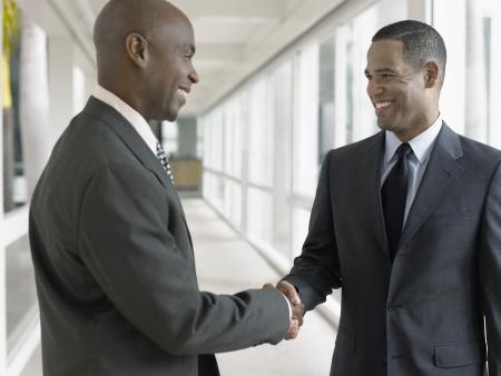 hombre calvo: Empresarios agitando las manos en el pasillo