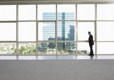 Homme d'affaires par fenêtre dans immeuble de bureaux