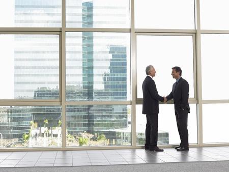 dandose la mano: Empresarios agitando las manos en edificio de oficinas LANG_EVOIMAGES