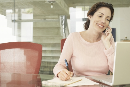 business roles: Businesswoman Using Cell Phone and Laptop