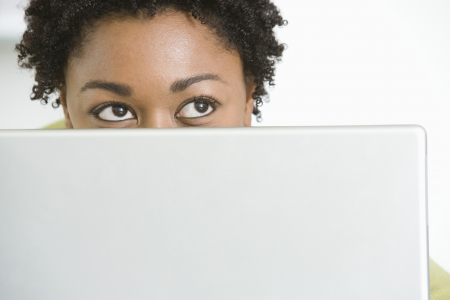 woman looking up: Mid-adult business woman peeking from behind laptop