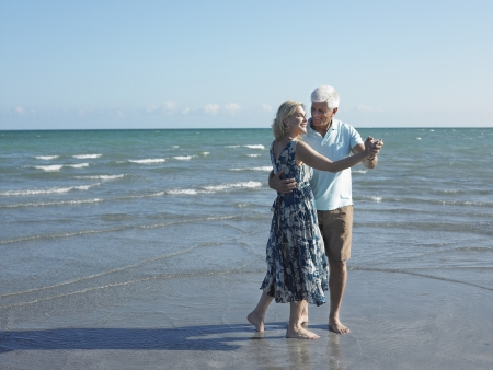 early sixties: Senior Couple Dancing on Beach