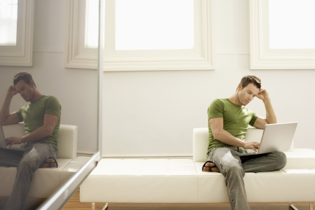 Man Using Laptop on Modern Sofa Stock Photo - 18833981