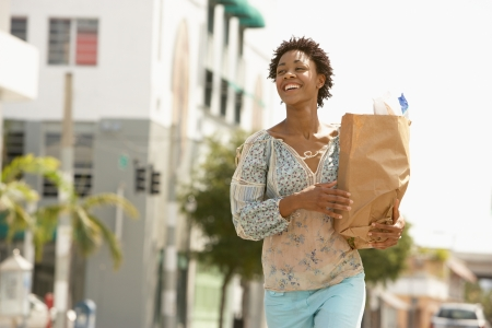 one mid adult woman only: Smiling young woman carrying groceries portrait LANG_EVOIMAGES
