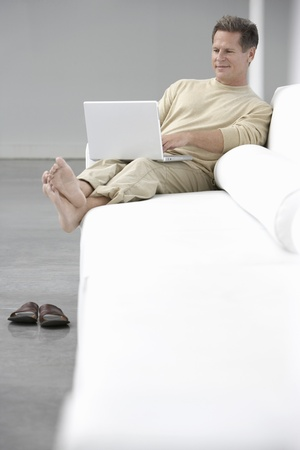 Man using laptop on sofa in living room Stock Photo - 19075558