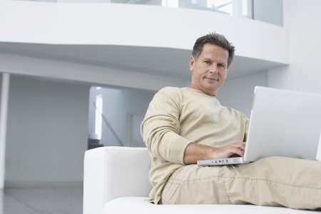 Man using laptop on sofa in living room portrait Stock Photo - 19184586