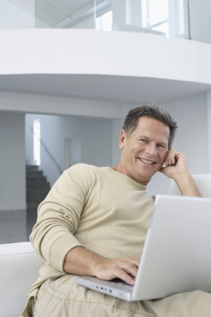 Man with laptop in living room smiling portrait Stock Photo - 19108188