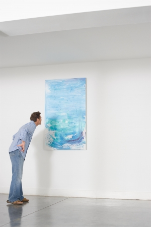 art gallery: Man contemplating paintings in gallery LANG_EVOIMAGES