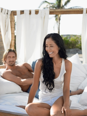 partially nude: Couple on bed on beach