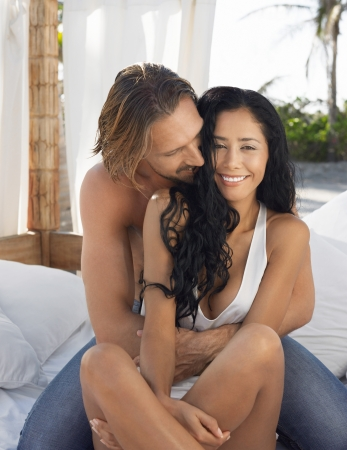 partially nude: Couple embracing on bed outside