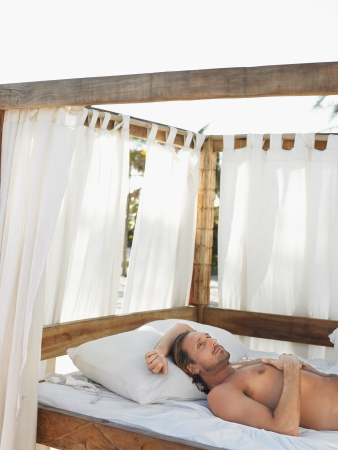 four poster bed: Man lying on four poster bed on beach half length