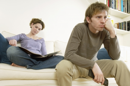 sexes: Young Man Watching Television with woman reading magazine behind
