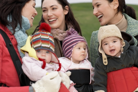 slings: Three mothers with babies in slings chatting outdoors LANG_EVOIMAGES