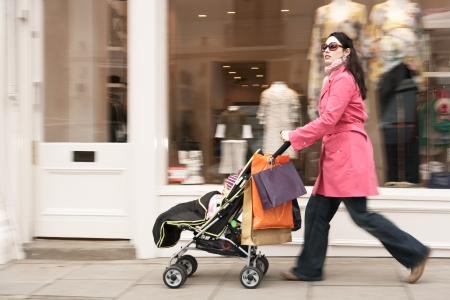 shopping buggy: Mother pushing stroller by clothes shop on street LANG_EVOIMAGES