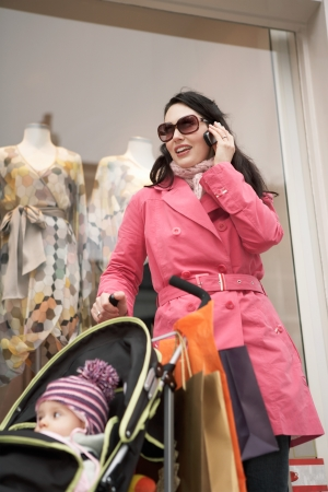 shopping buggy: Mother with baby standing in front of shop using mobile phone
