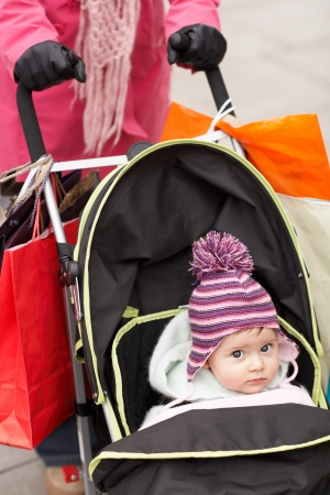 shopping buggy: Mother walking with baby in stroller close up on baby LANG_EVOIMAGES