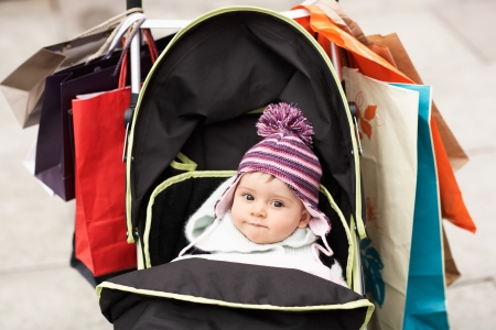 shopping buggy: Baby sitting in stroller hung with shopping bags outdoors