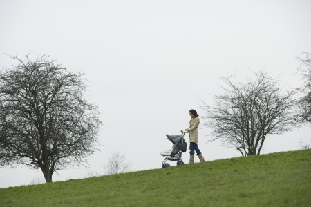 unknown age: Mother pushing stroller in park LANG_EVOIMAGES
