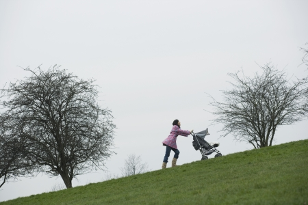 unknown age: Mother pushing stroller uphill