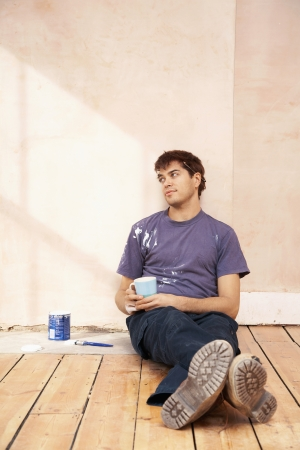 Man sitting on floor of unrenovated room holding coffee mug Stock Photo - 19075610