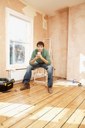 step ladder: Man sitting on step ladder in unrenovated room